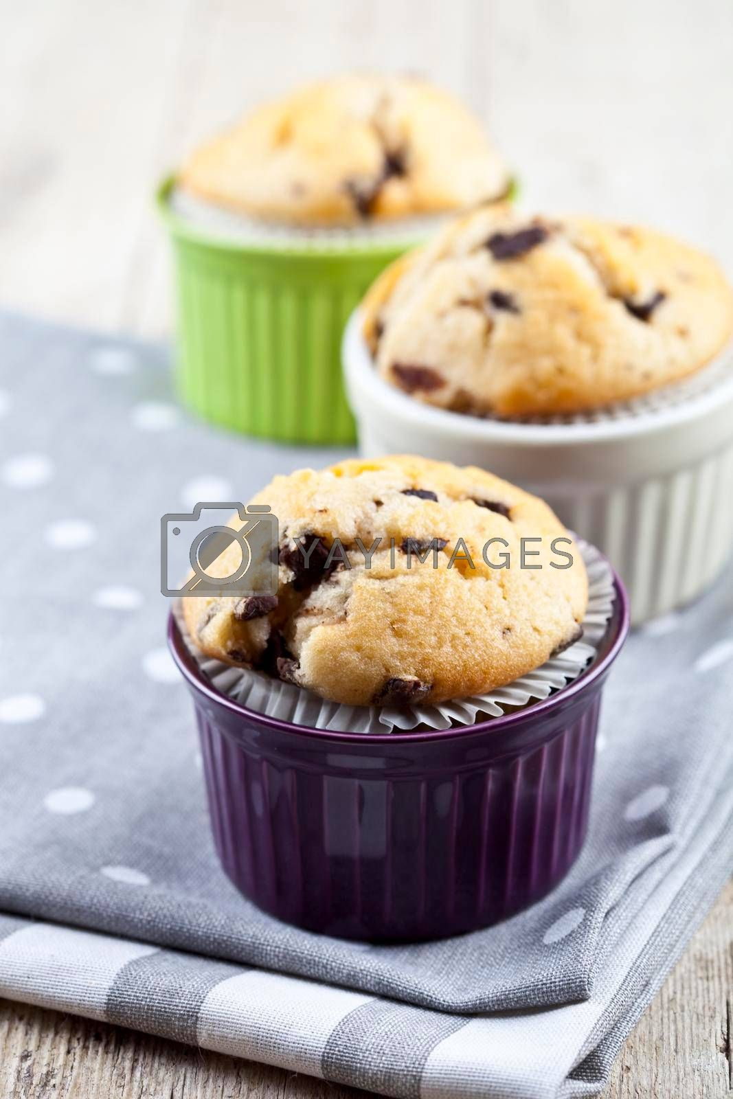 Three homemade fresh muffins on colorful ceramic bowls on linen napkins on rustic wooden table background.