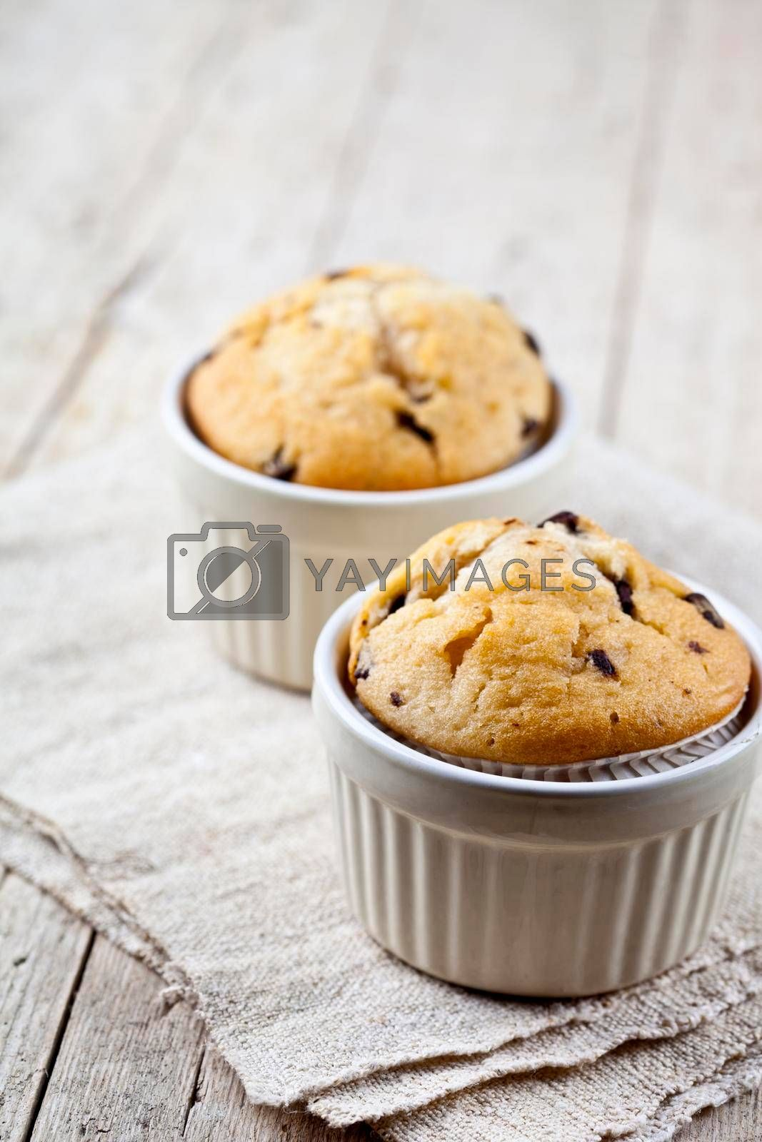 Two homemade fresh muffins on ceramic white bowls on linen napkin on rustic wooden table background.
