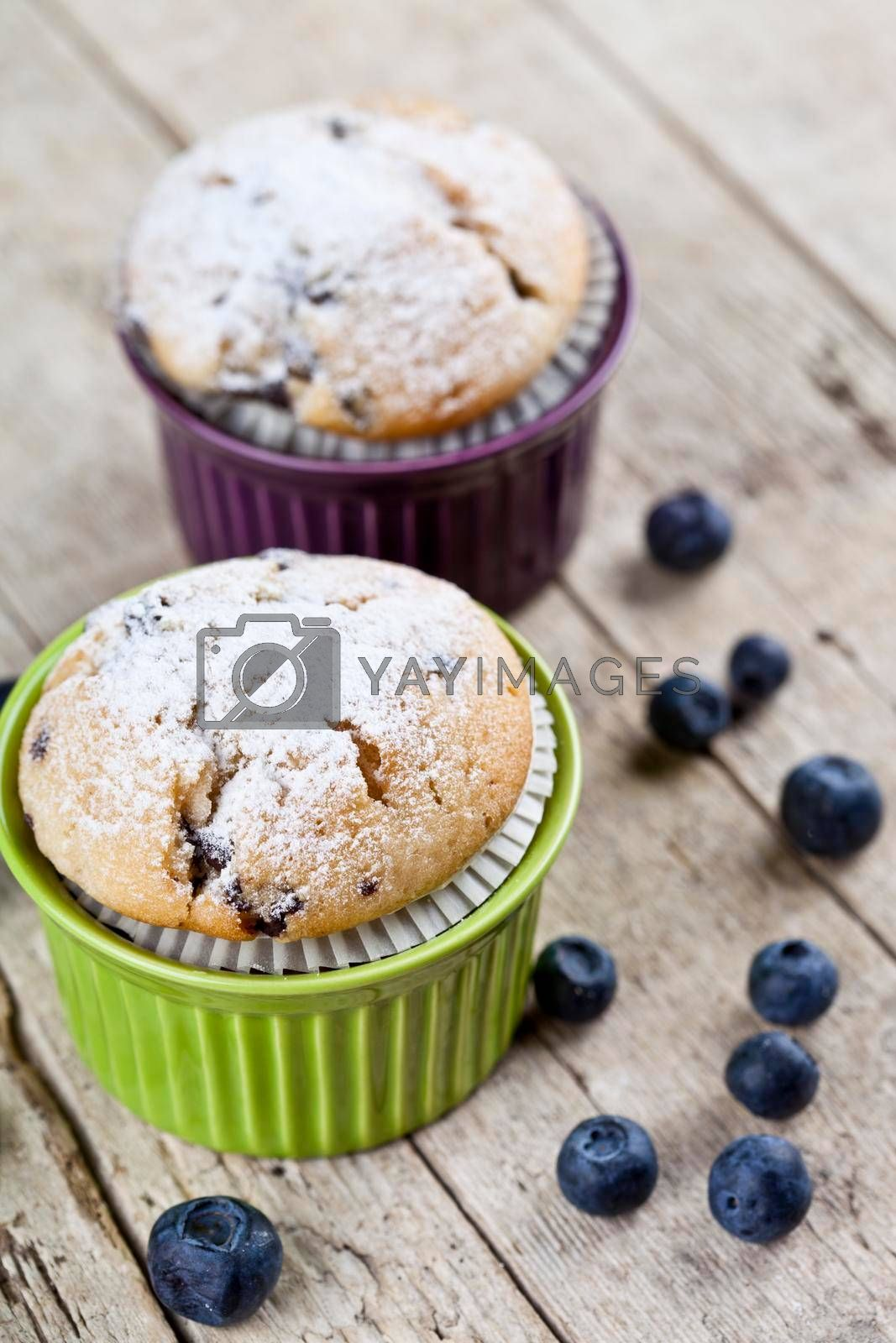 Two homemade fresh muffins on ceramic green and purple bowls with blueberries on rustic wooden table background.