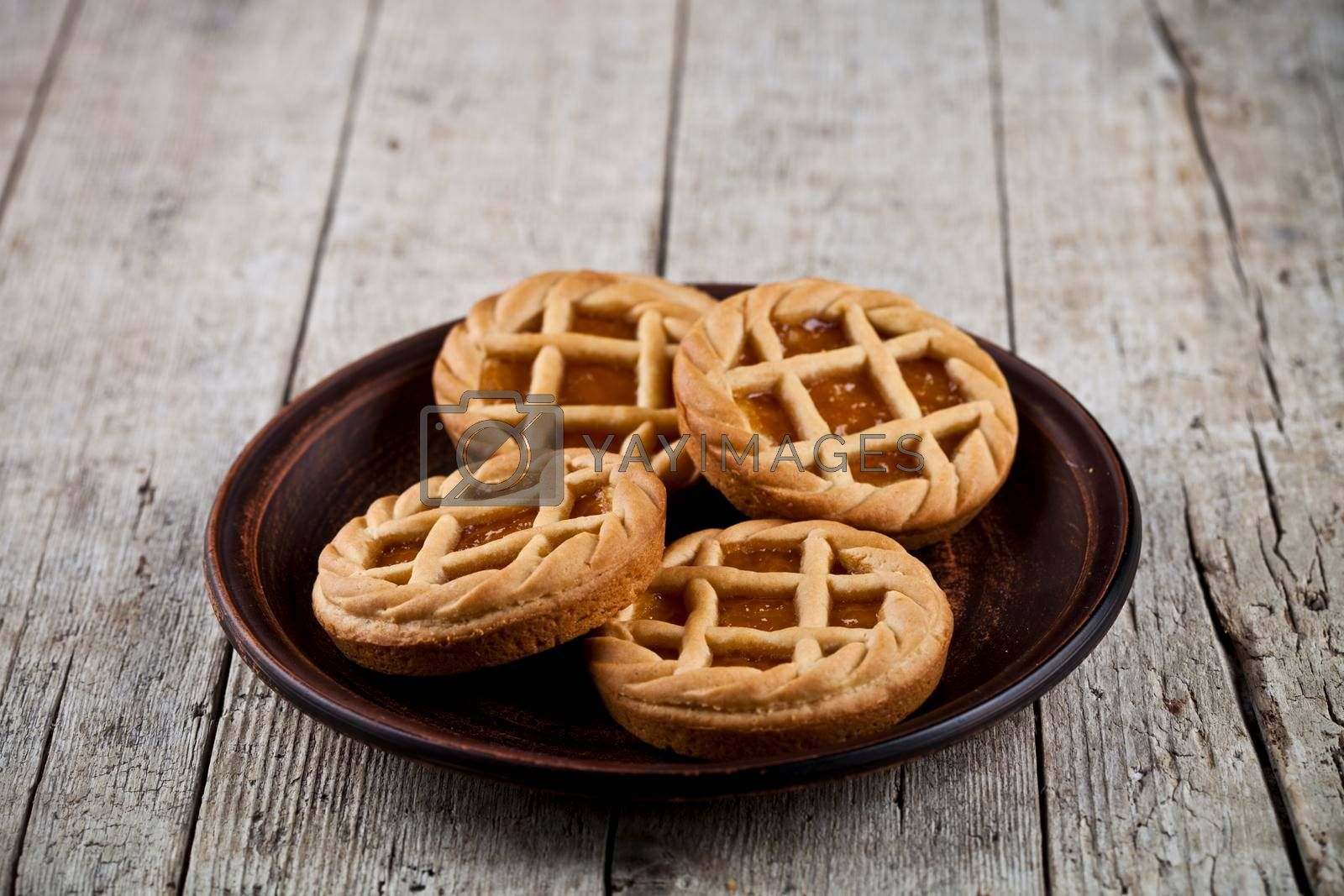 Fresh baked crostata with marmalade or apricot jam filling on brown plate on rustic wooden table background.