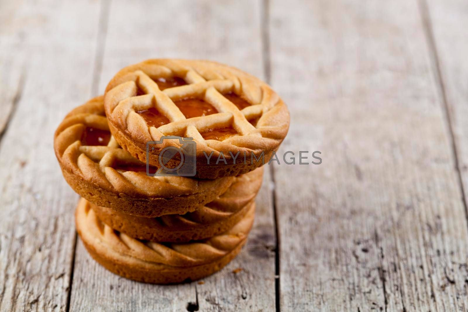 Fresh baked tarts with marmalade or apricot jam filling on on rustic wooden table background. With copy space.