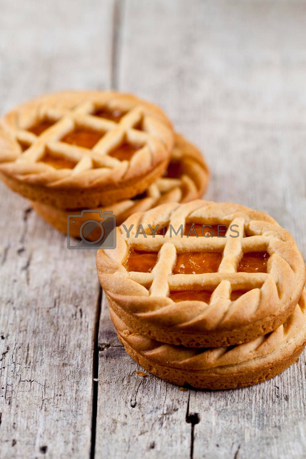 Fresh baked tarts with marmalade or apricot jam filling on on rustic wooden table background.