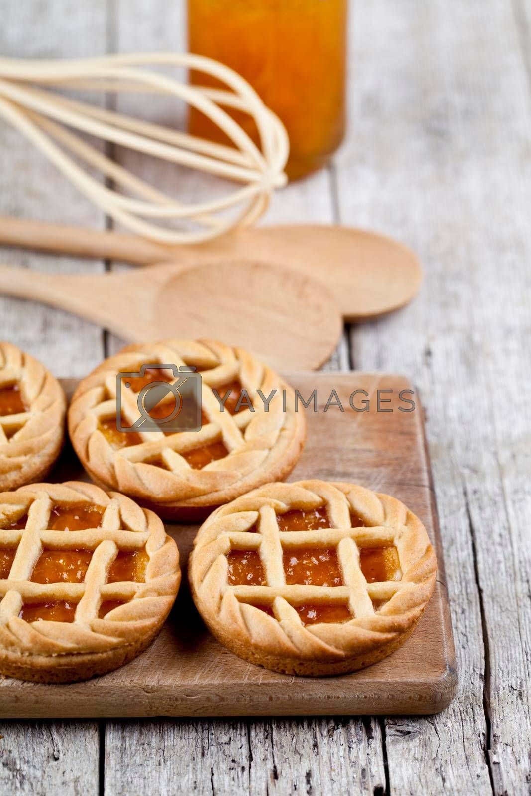 Fresh baked tarts with marmalade or apricot jam filling and on cutting board and kitchen bakery utensil on on rustic wooden table background.