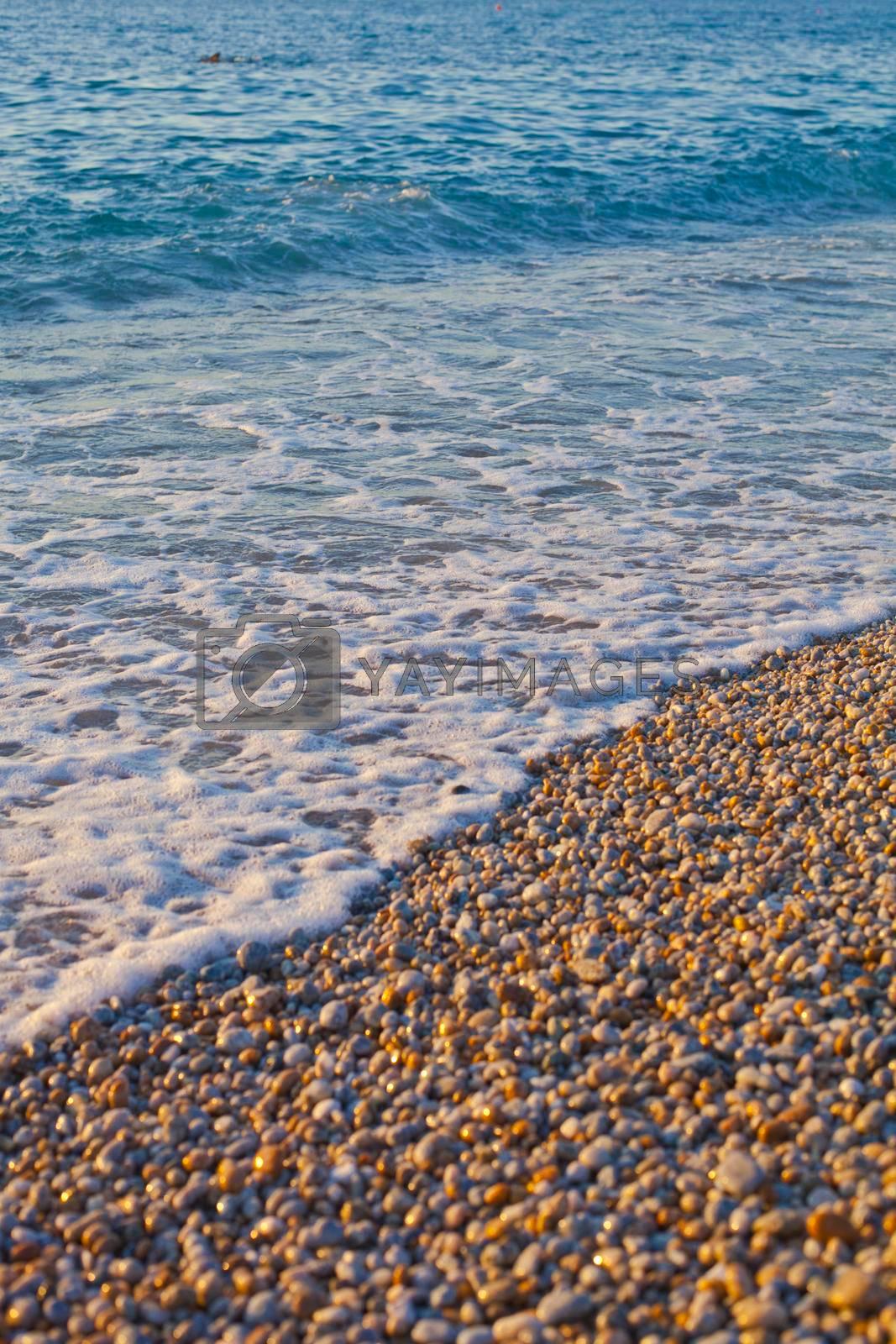 Pebble stones by the sea. Waves of blue Tyrrhenian sea. Calabria, Italy.