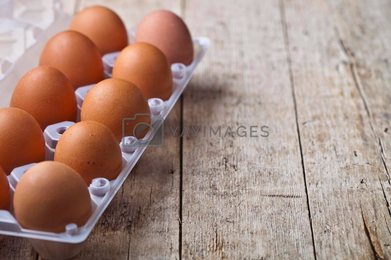 Fresh chicken eggs on plastic container on rustic wooden table background. With copy space.