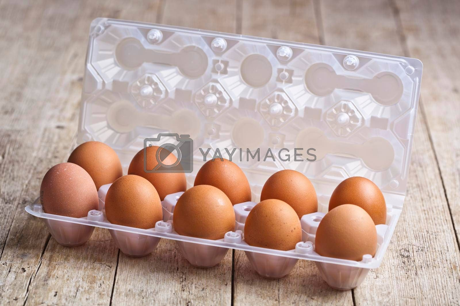 Fresh chicken eggs on plastic container on rustic wooden table background.