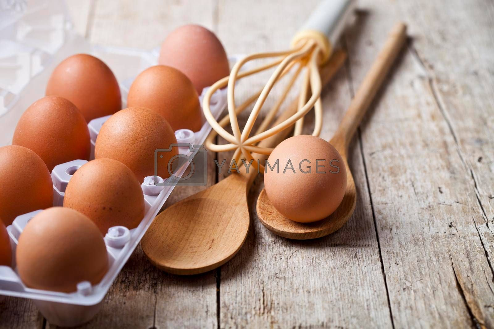 Fresh chicken eggs on plastic container and kitchen utensil on rustic wooden table background. Bakery tools with copy space.