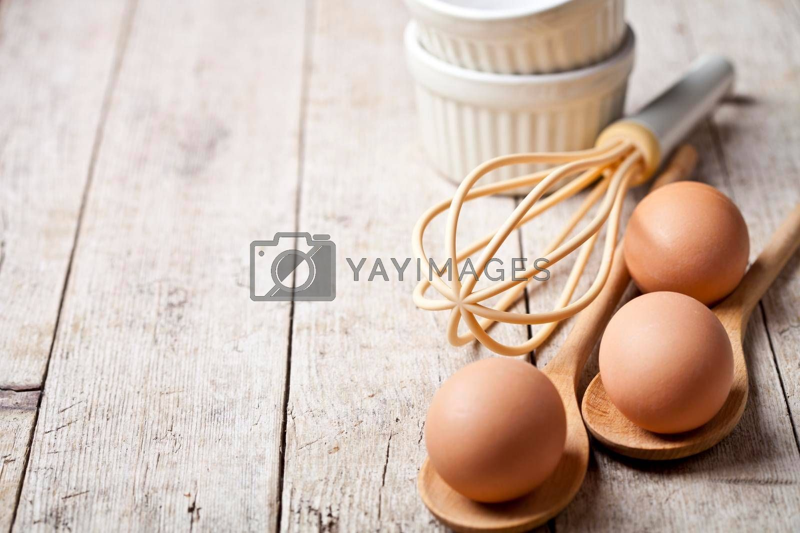 Fresh chicken eggs and kitchen utensil on rustic wooden table background. Bakery tools with copy space.