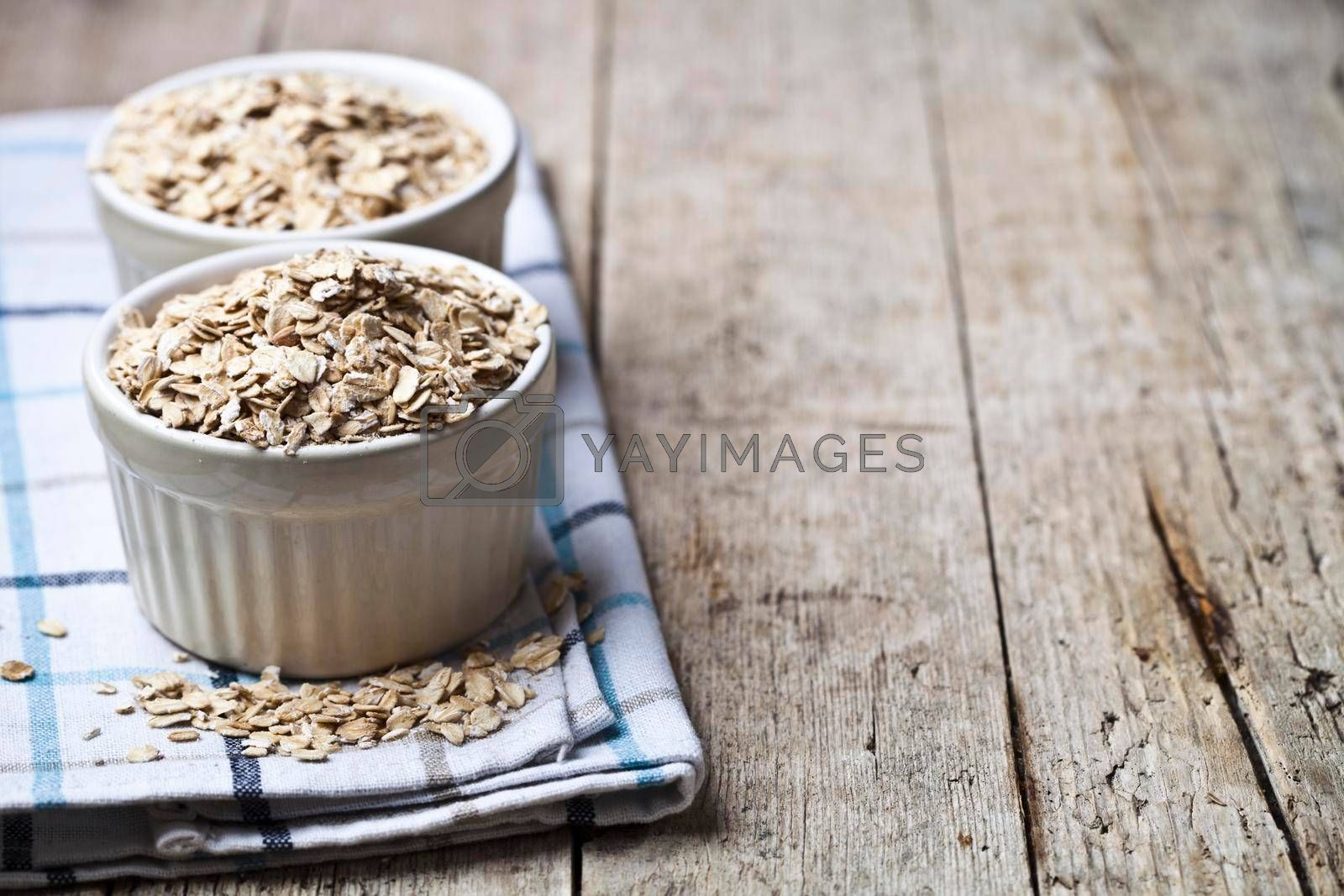 Oat flakes in ceramic bowls on linen napkin, golden wheat ears on rustic wooden background. Healthy lifestyle, healthy eating concept.