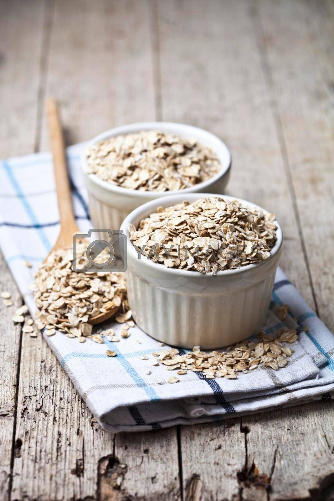 Oat flakes in ceramic bowls and wooden spoon on linen napkin, golden wheat ears on rustic wooden background. Healthy lifestyle, healthy eating concept.