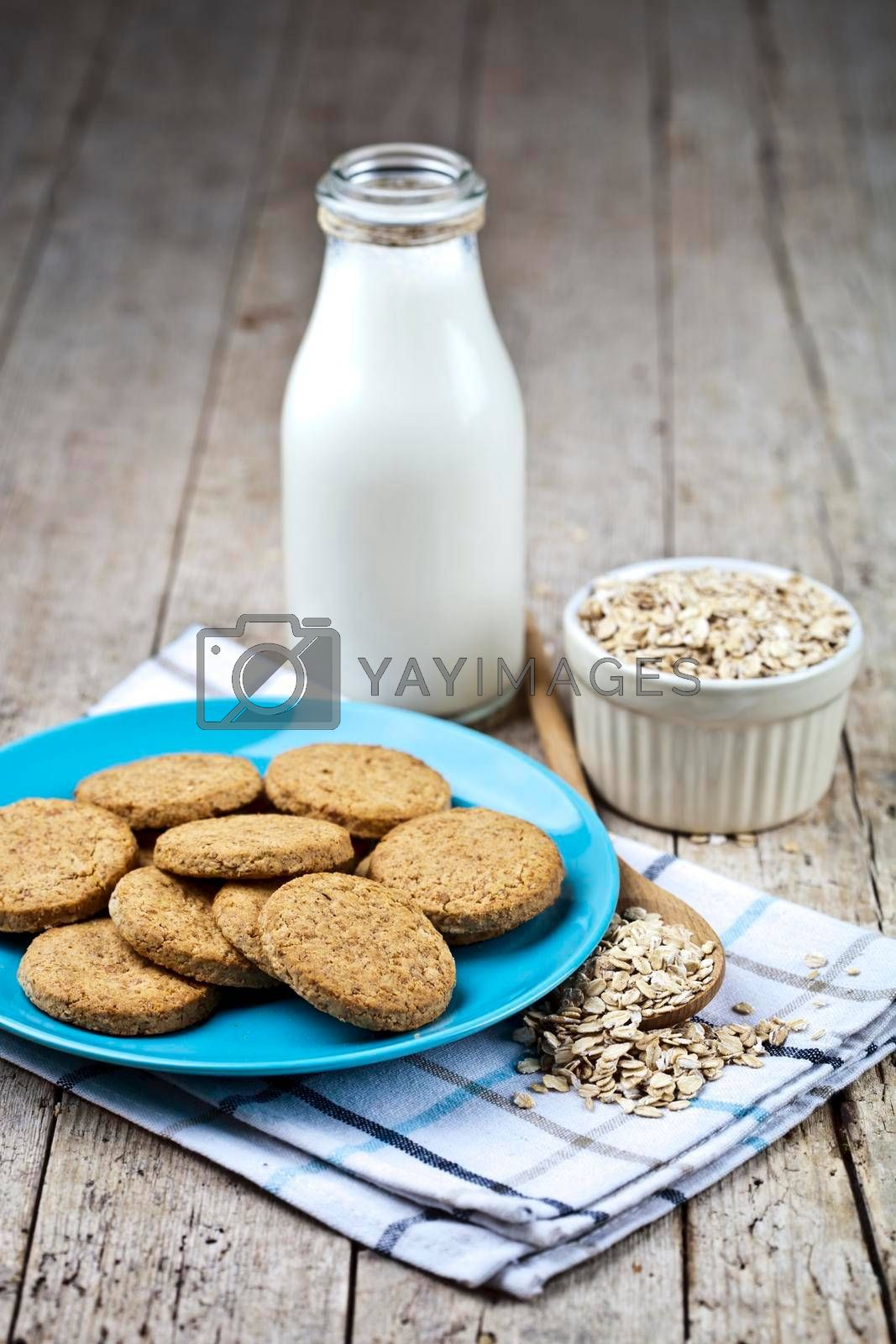 Fresh baked oat cookies on blue ceramic plate on linen napkin, bottle of milk and oak flakes on rustic wooden table background.