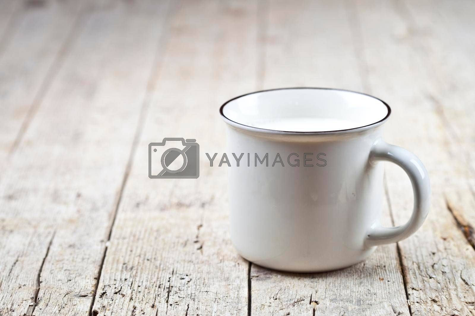 Fresh milk on white ceramic cup on rustic wooden table background. With copy space.