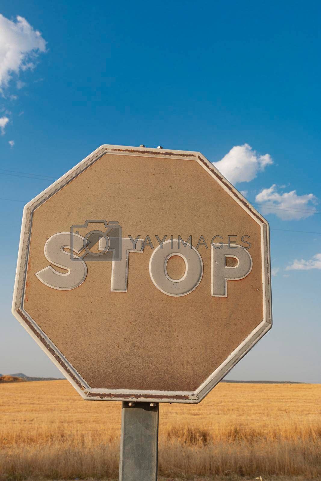 Old stop sign faded by the sun on a road in southern Spain