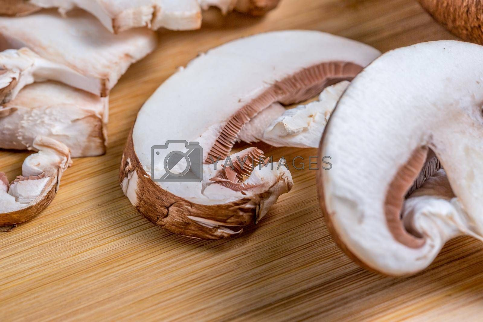 Royal champignons, Parisian champignons, chopped mushrooms on bamboo wooden chopping board, close-up. Dark wooden background. Side view.