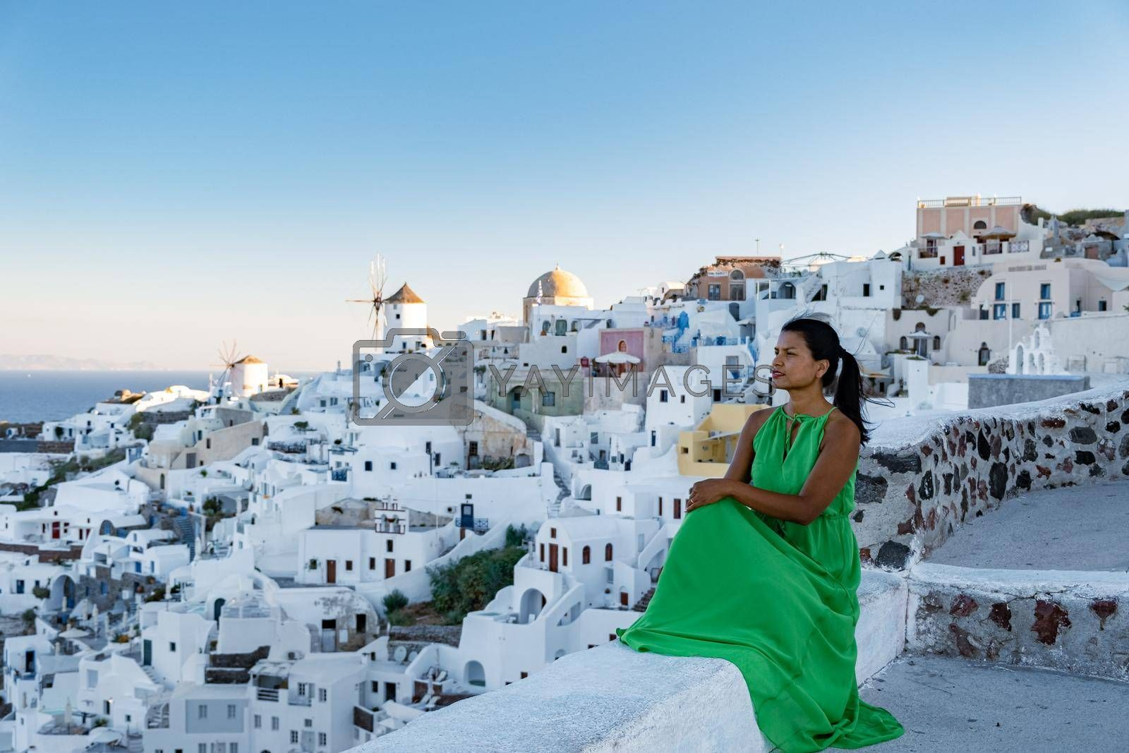 Oia village Santorini with blue domes and white washed house during sunset at the Island of Santorini Greece Europe, sunrise Santorini, woman watching sunset