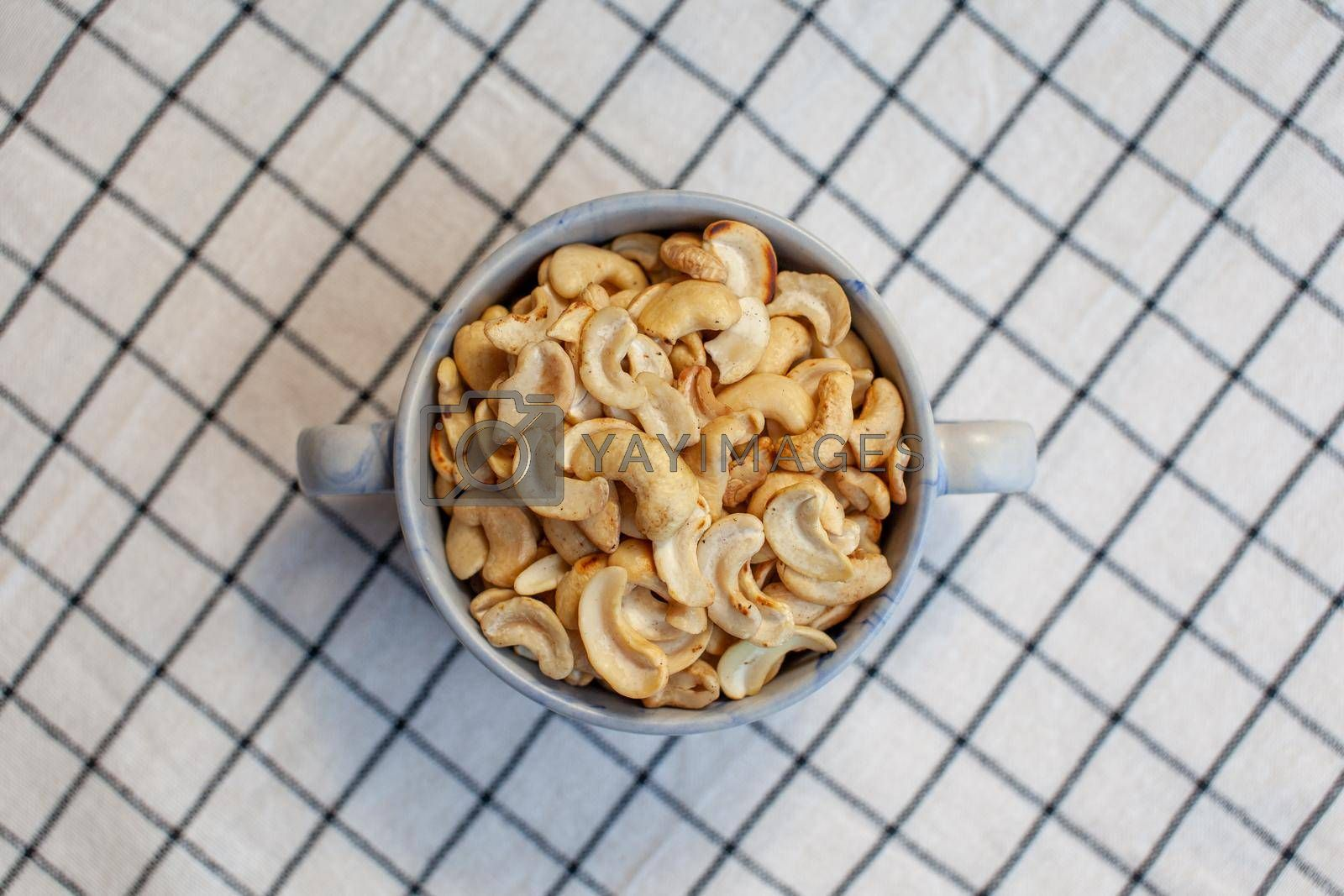 A plate of cashew nuts on a nice napkin. Delicious and healthy food. There is a place for the text.
