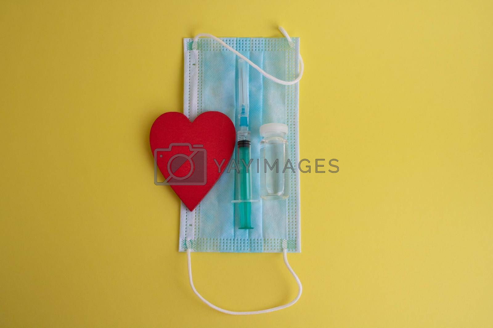 On a yellow background-a mask, a syringe, a bottle of vaccine and a red heart. The concept of medicine and health care.