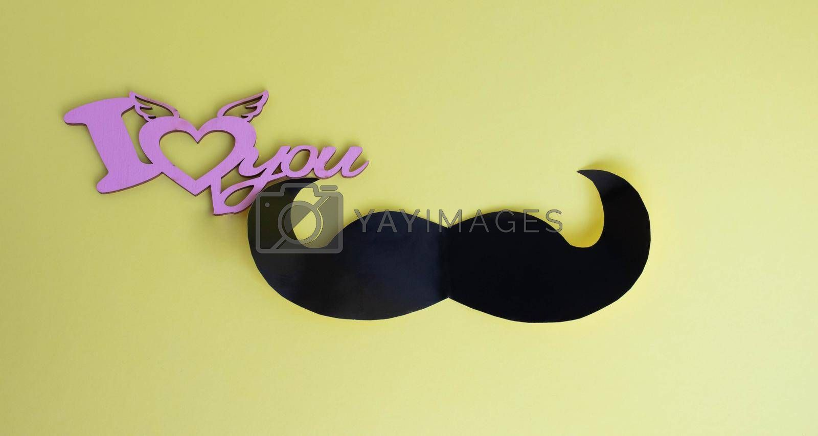Father's Day concept. Black mustache and I love you sign on yellow paper background by lapushka62