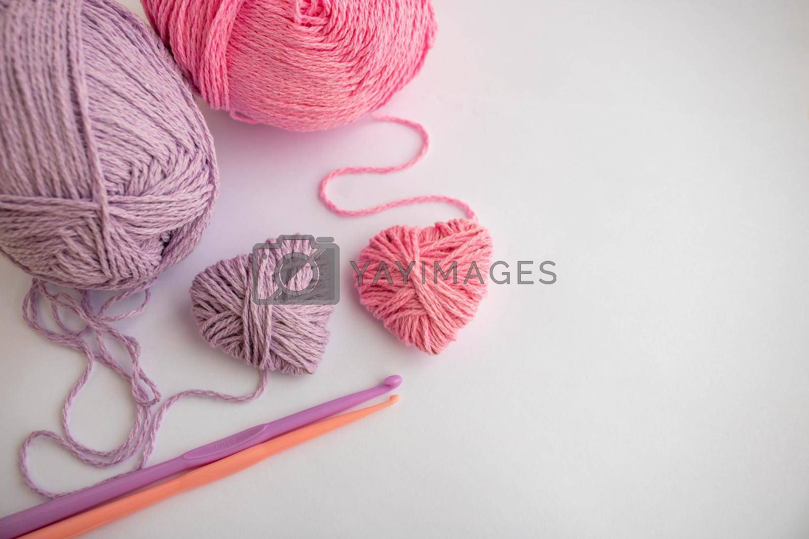 Threads,hooks, and two hearts lay on a white background.Holiday card, background. The concept of Valentine's Day, March 8, Mother's Day. Space for your text by lapushka62