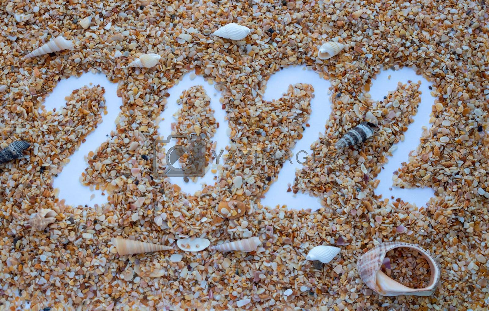 The number 2022 is drawn on the sand of shells.New Year's Calendar by lapushka62