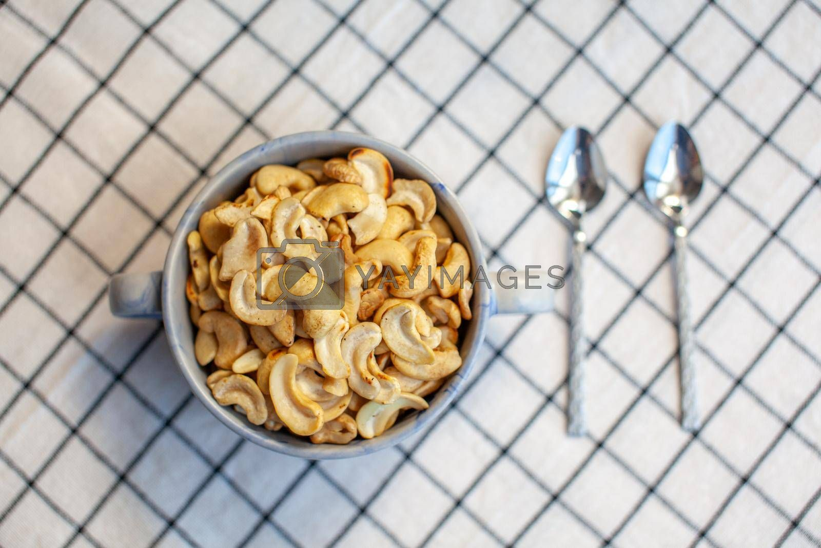 A plate of cashew nuts on a nice napkin and two spoons next to it. Delicious and healthy food for a snack. There is a place for the text.