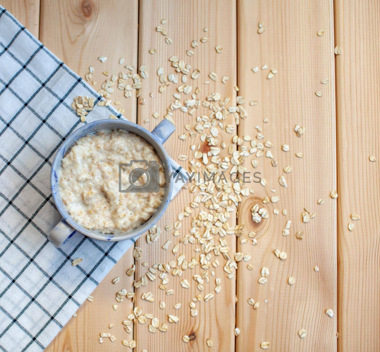 Fresh oatmeal porridge in a plate on a beautiful napkin and on a wooden table. A fresh and healthy breakfast.