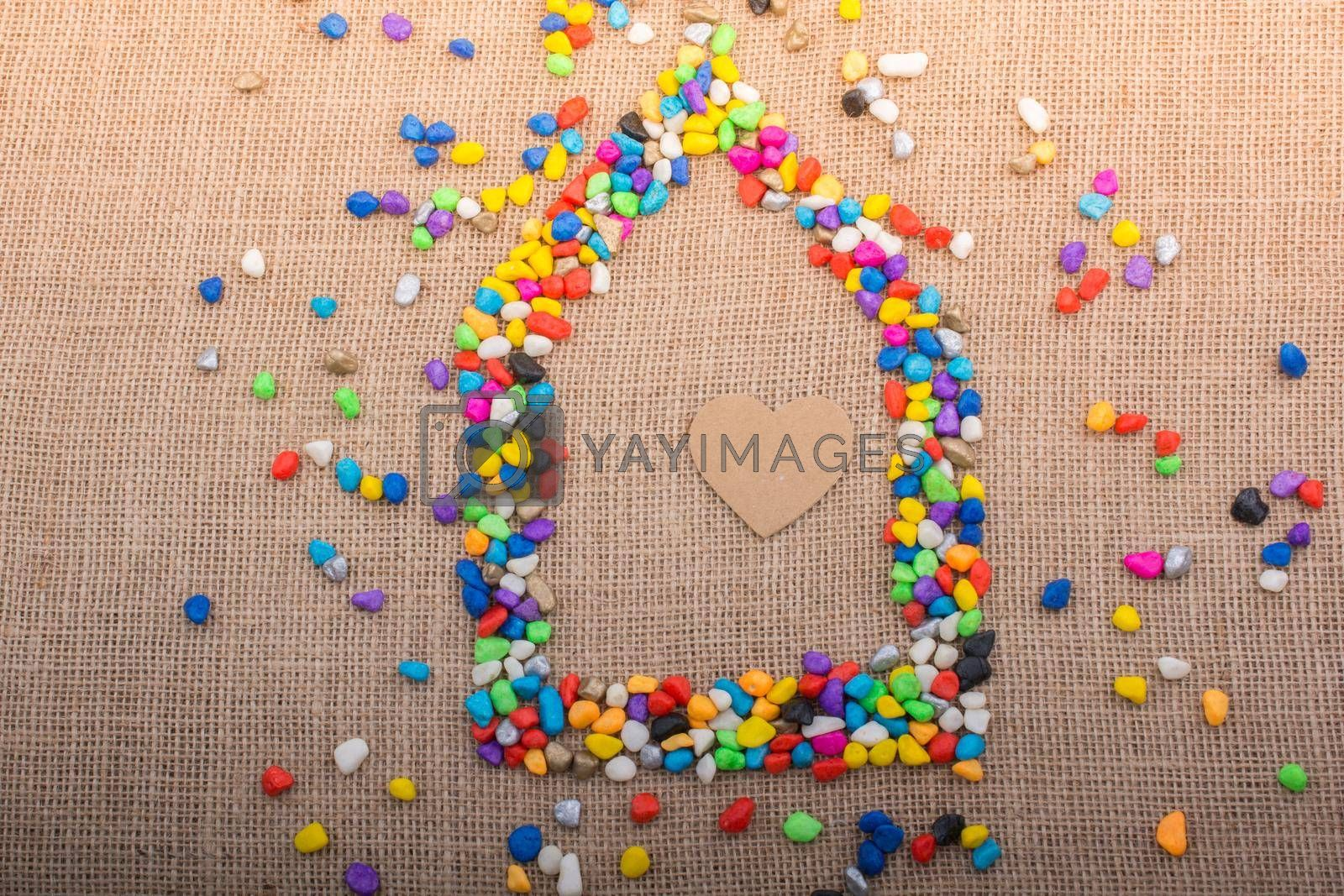 Heart in the house form shaped by colorful pebbles