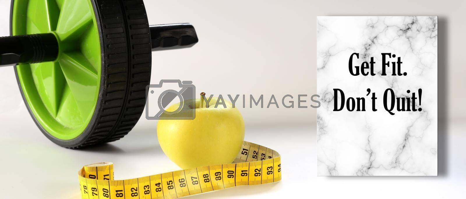 Healthy lifestyle motivational quote. Diet fitness and Healthy life Concept. Motivational Quote text Get Fit. Don't Quit. Apple, measure tape, sport home gym equipment ab roller for diet slimming
