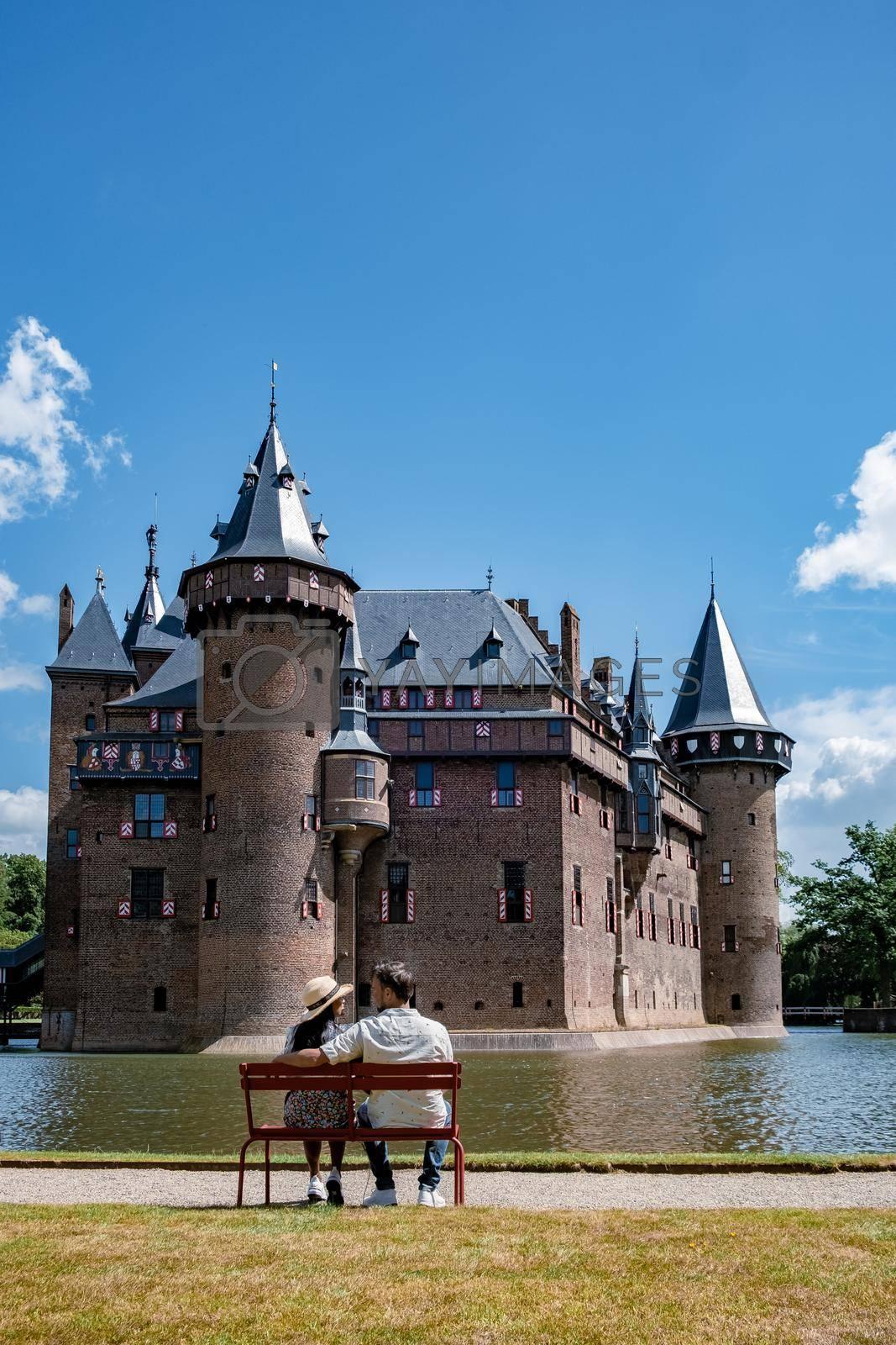 Castle de Haar Utrecht, couple men and woman mid age European and Asian visit De Haar Castle in Dutch Kasteel de Haar is located in Utrecht Netherlands during Spring with flowers in the garden