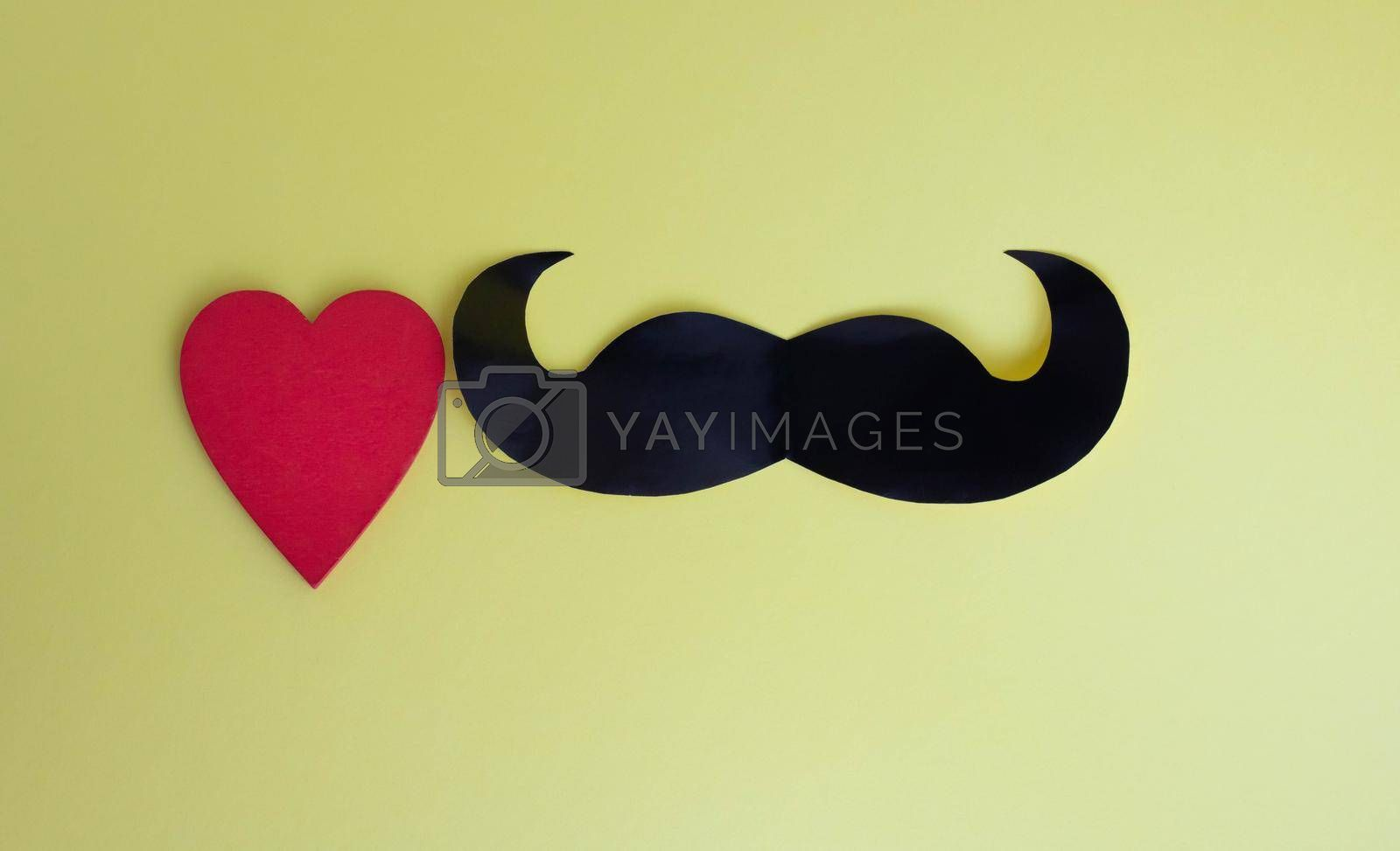 Father's Day concept. Black mustache and red heart on a yellow paper background by lapushka62