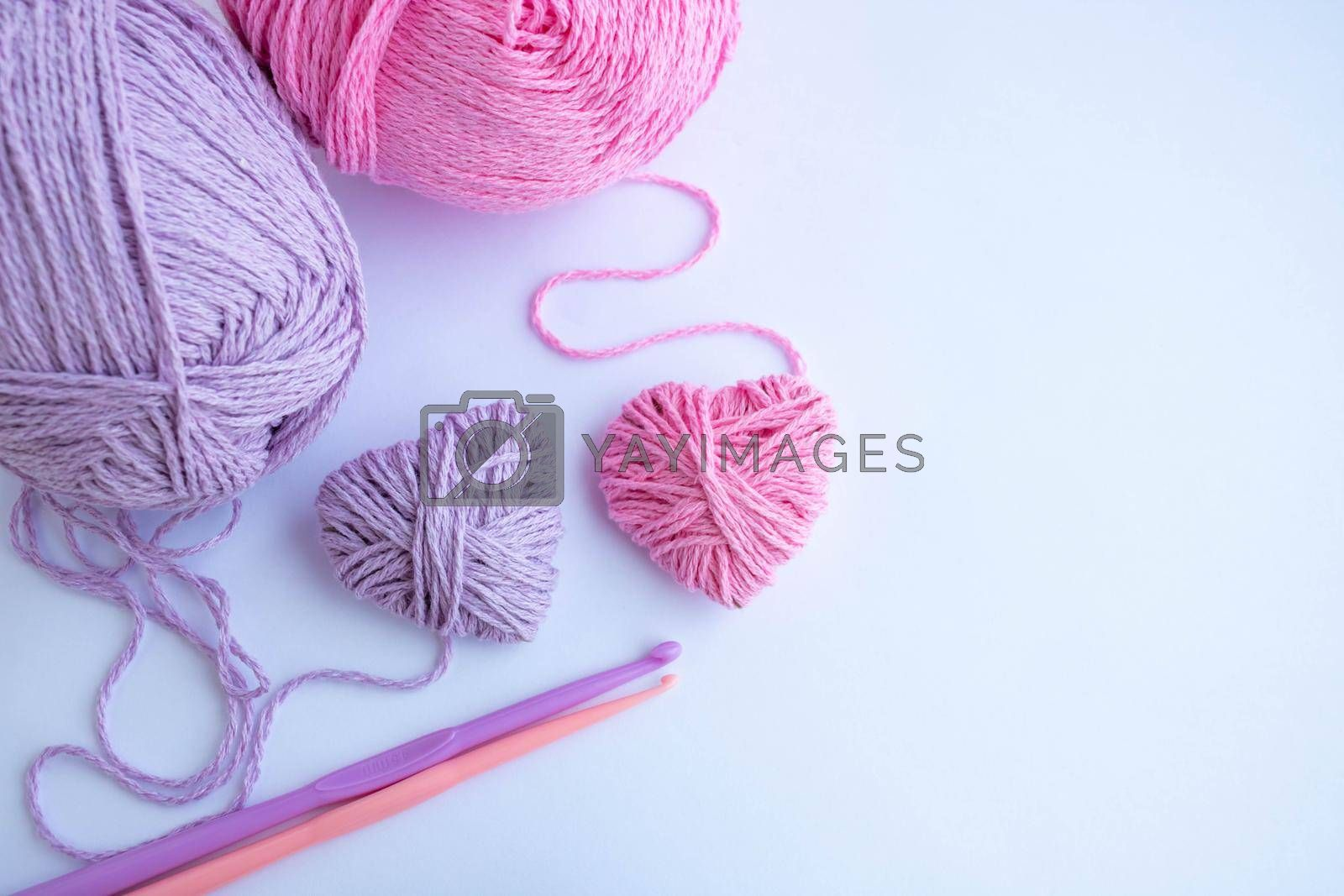 Threads,hooks, and two hearts lay on a white background.Holiday card, background. The concept of Valentine's Day, March 8, Mother's Day. Space for your text.