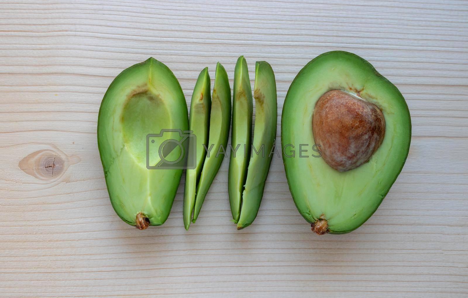 Slices of ripe avocado lie on a light cutting board by lapushka62