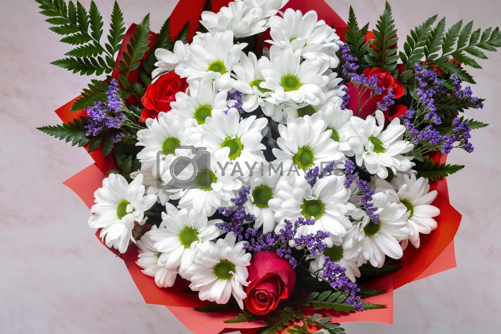 A beautifully designed bouquet of white chrysanthemums and red roses on a light background. Top view, close-up.