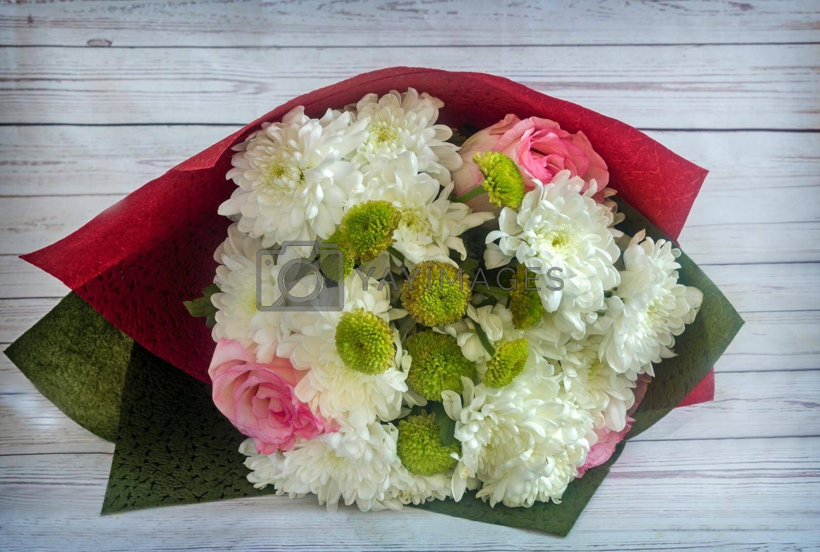 Beautiful bouquet of roses and chrysanthemums in decorative packaging.