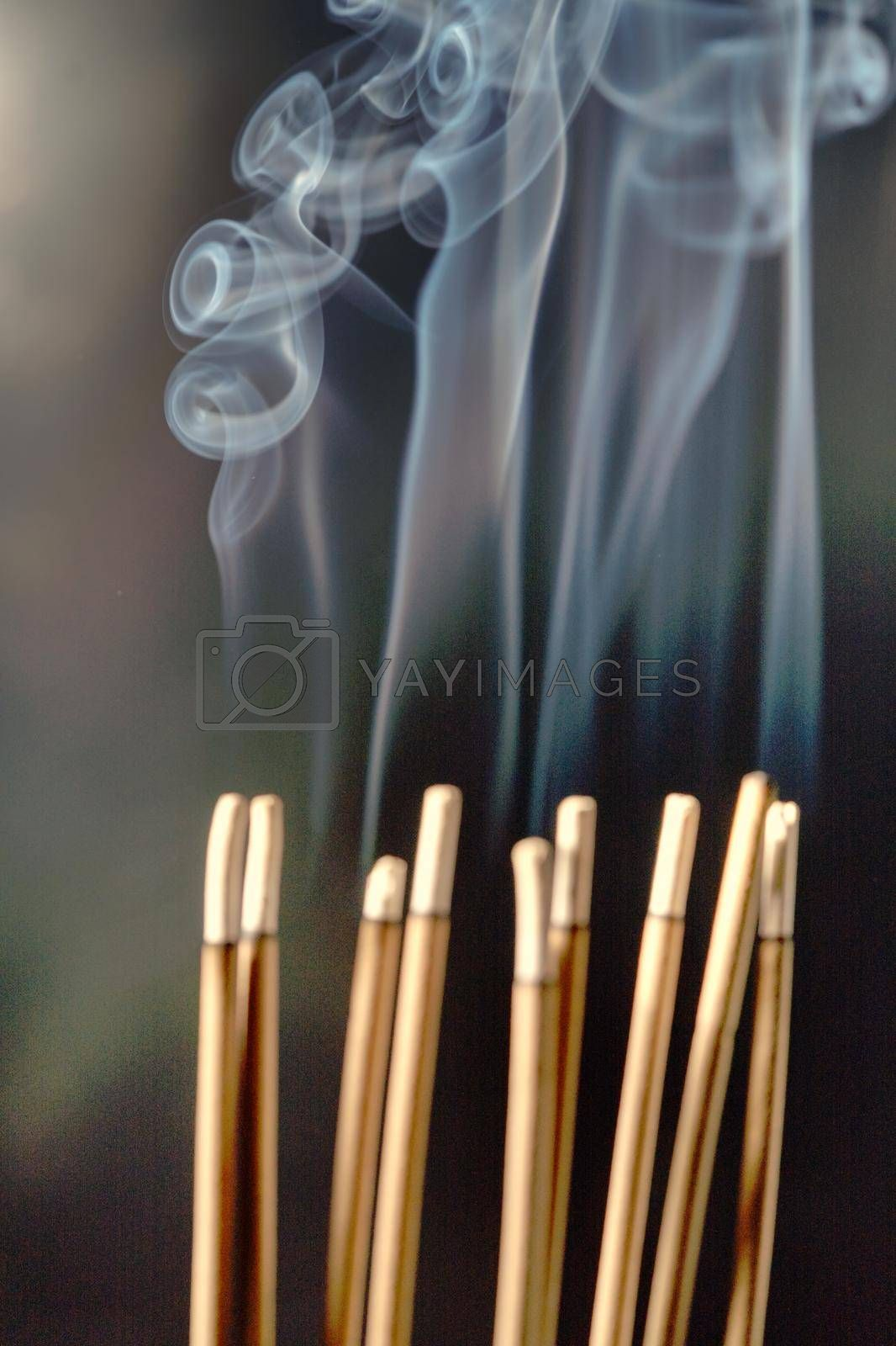 Burning incense, white smoke, black background, used as a worship background image, a sacred object of Buddhist beliefs, focus on the smoke.