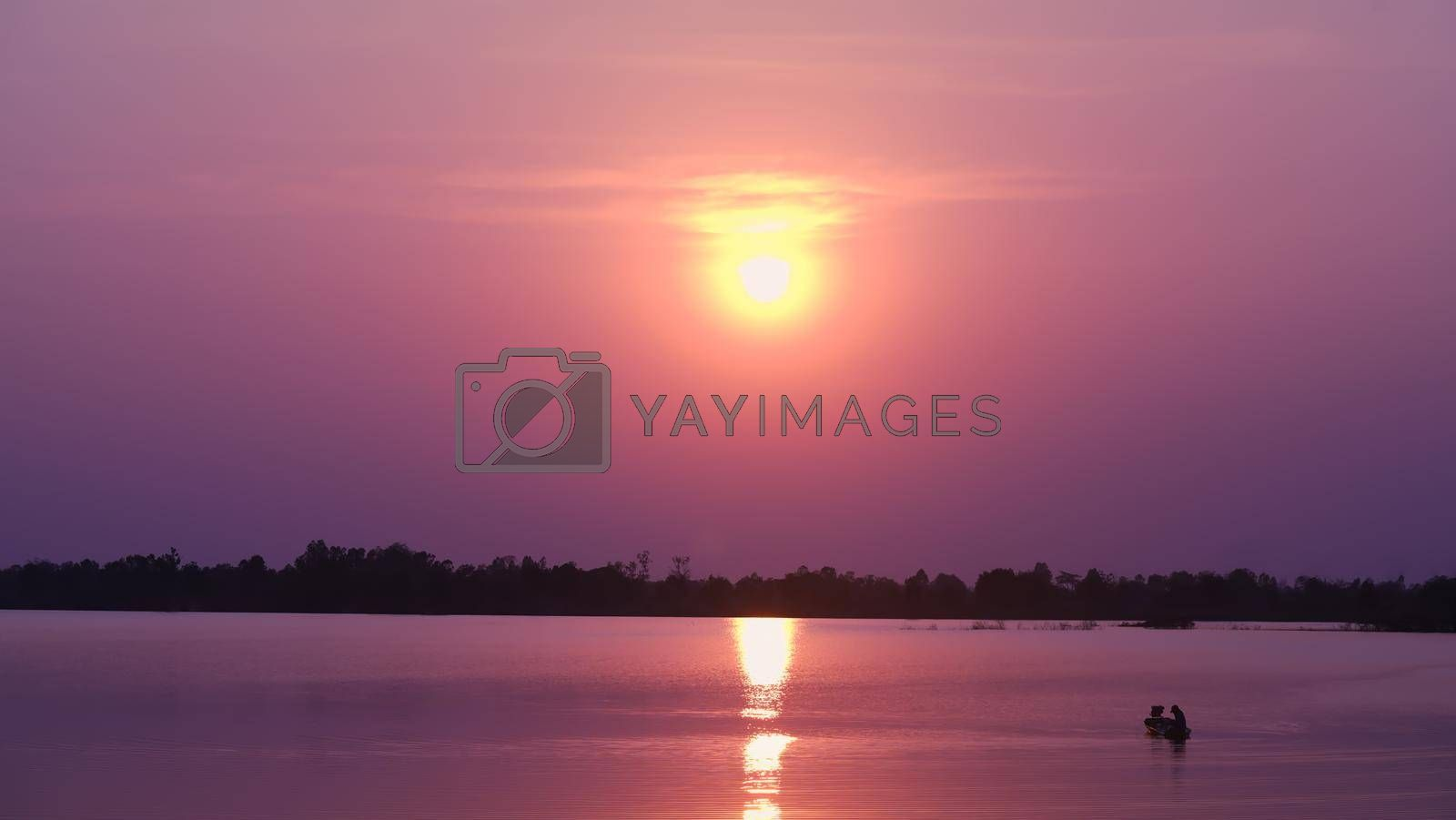 The scenery along the lake has an orange sky and a beautiful sunset.
