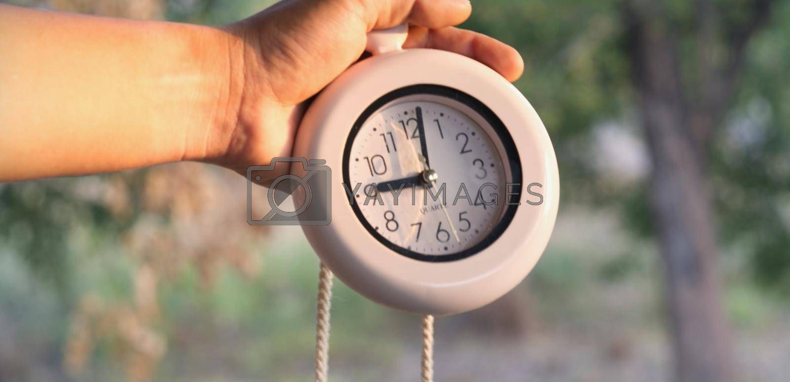 Man hand holding alarm clock showing nine o'clock time concept to start a new day.