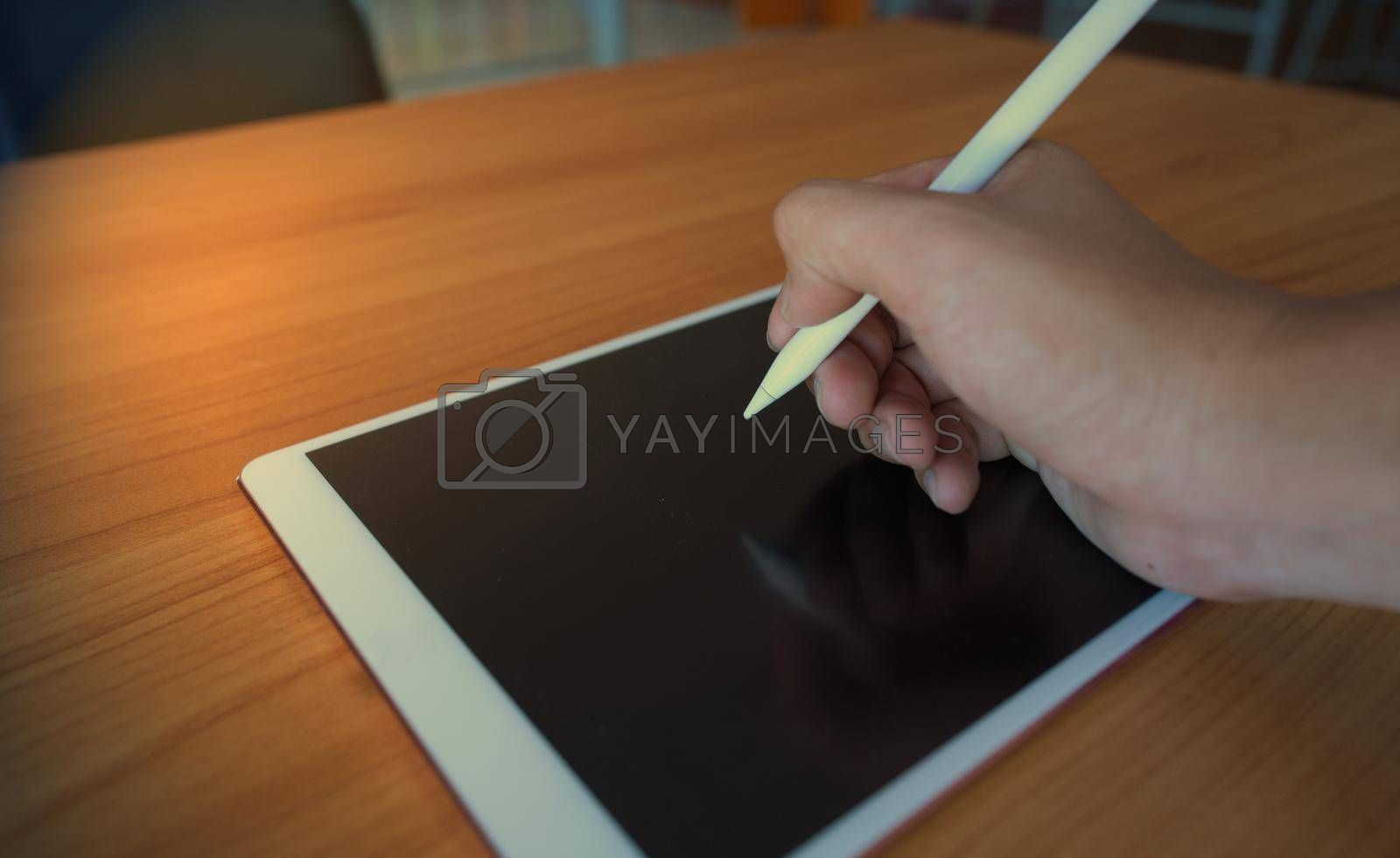 A man writing on the tablet with an electronic pencil on a wooden table