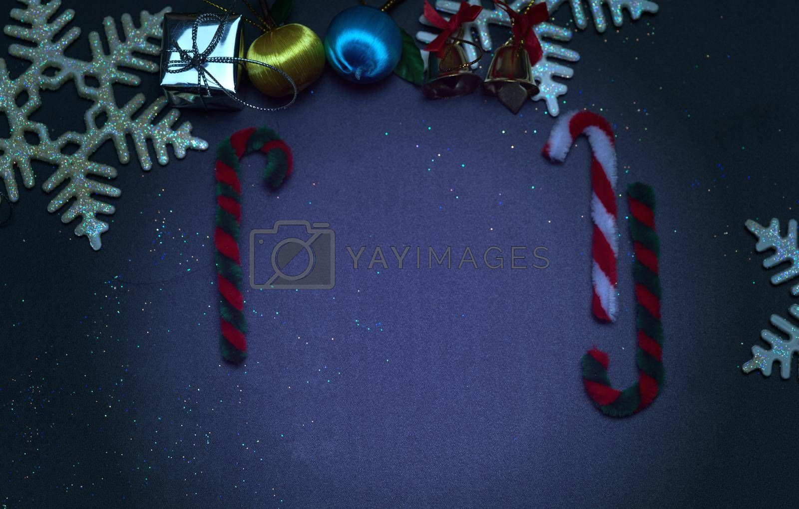 Elegant Christmas background with golden snowflakes and bells with shining gift boxes, black wood texture background.