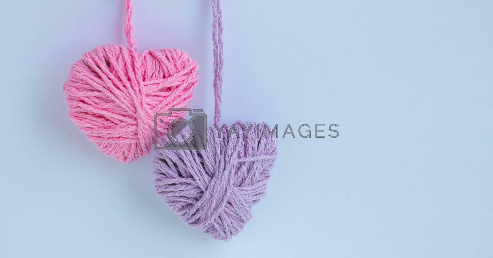 Two thread hearts hang on a white background. Holiday card, background. The concept of Valentine's Day, March 8, Mother's Day.