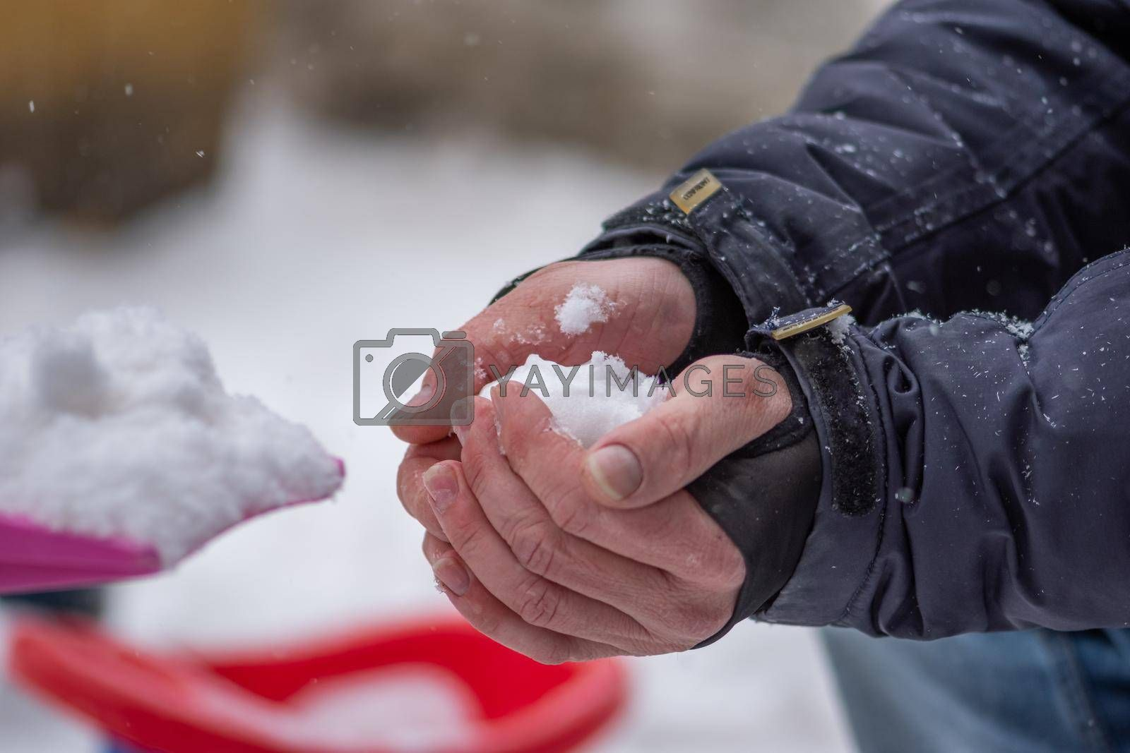 Closeup view of a person making a snowball in his hands standing outside dressed for winter