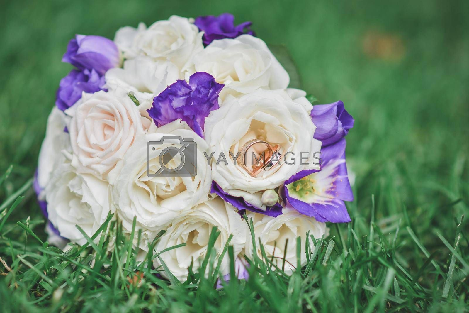 A small bouquet with two wedding rings on the green grass. Selective defocusing.