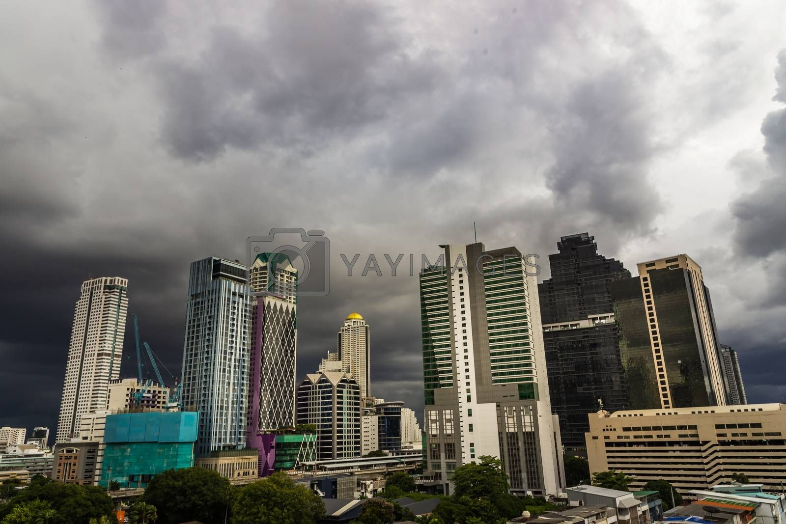 Dark storm clouds before rain of Bangkok city with district office building and center for business in the evening. Selective focus.