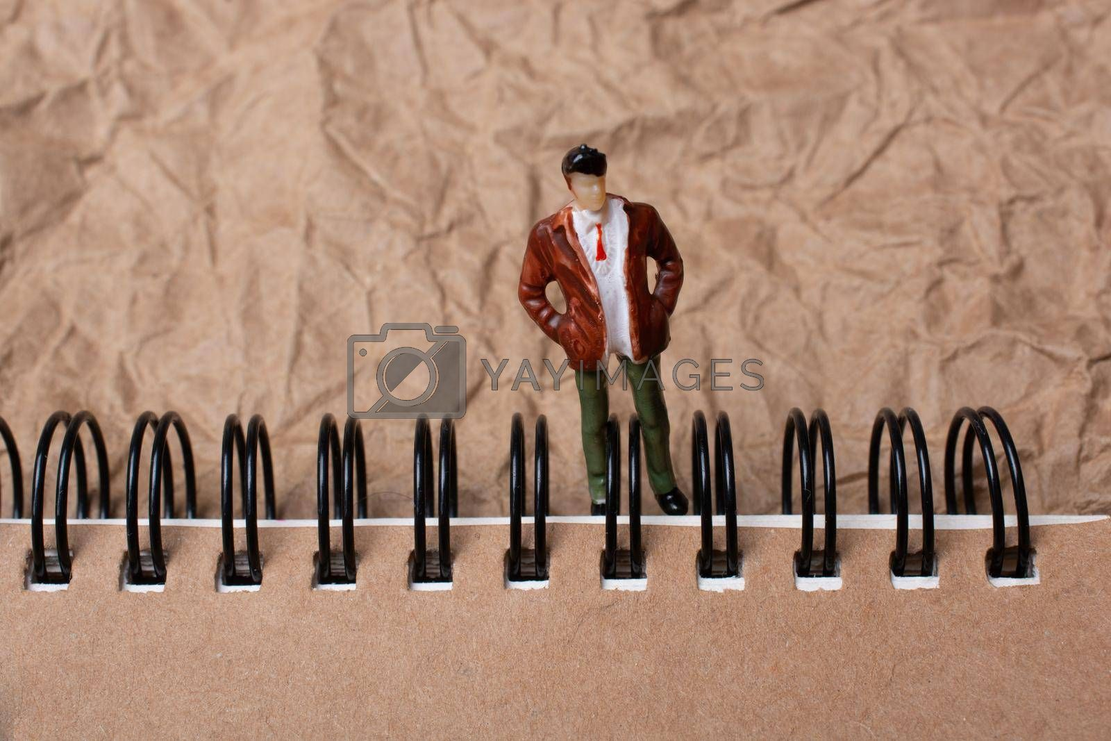 Figurine standing beside spiral notebook