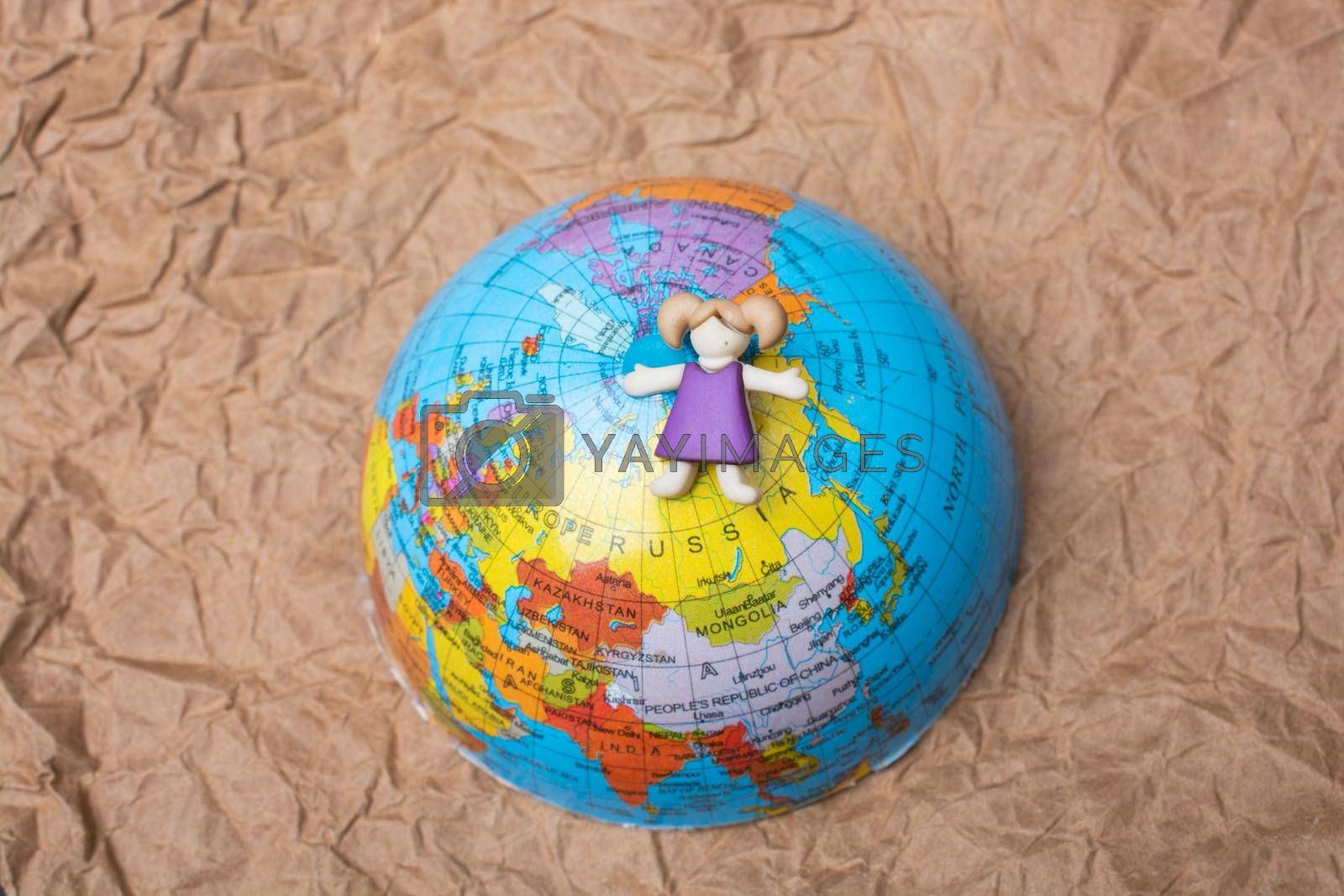 Miniature girl on top of globe as education and business concept