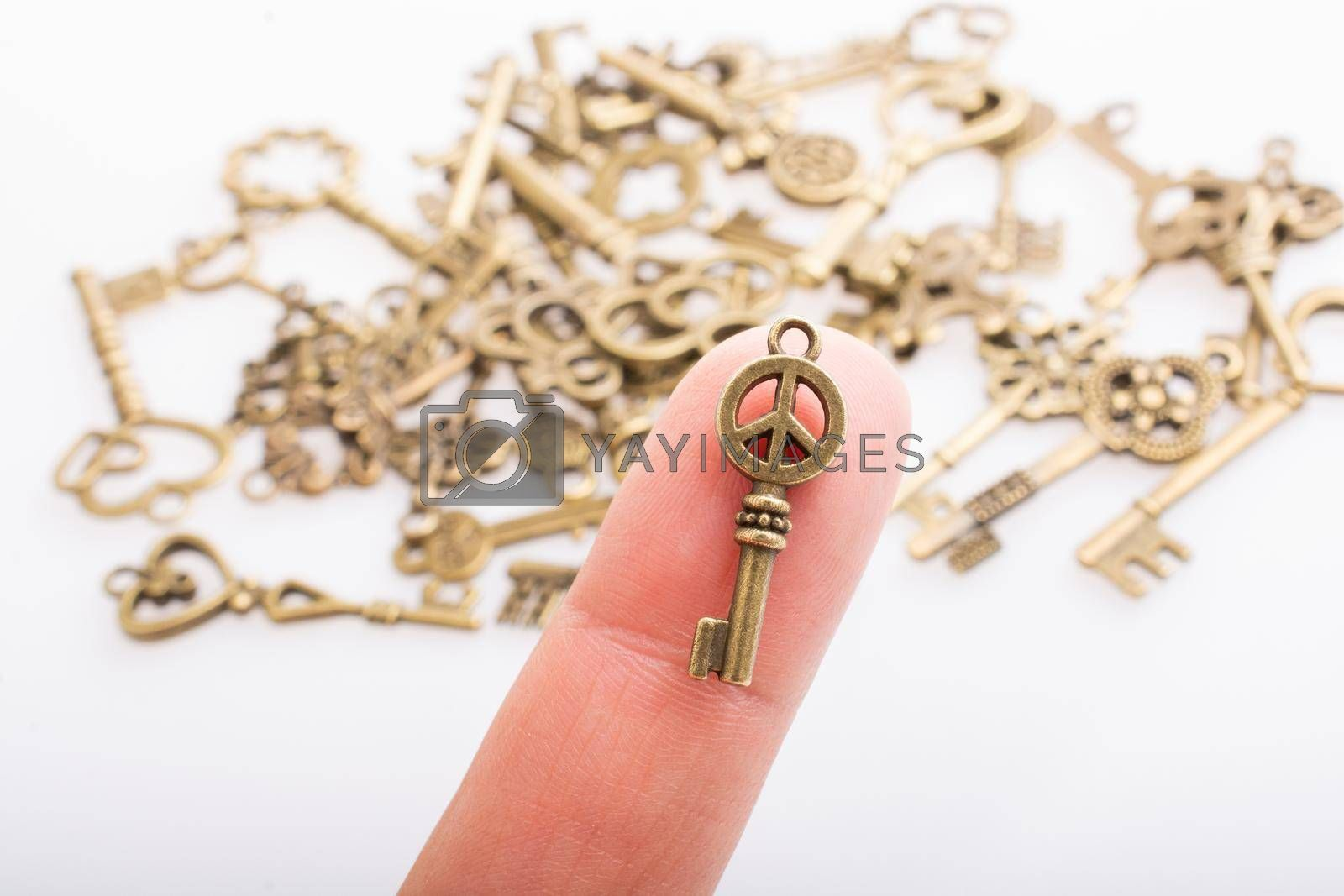 Peace symbol key in hand over and retro style metal keys