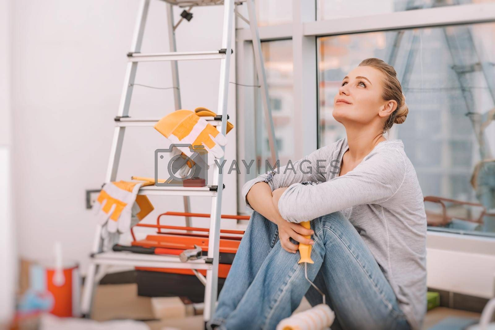 Dreamy Girl Sits on the Floor in the Flat with a Paint Roller and Imagines what a Cool Renovation She Will Make. Repairs in the New Apartment.