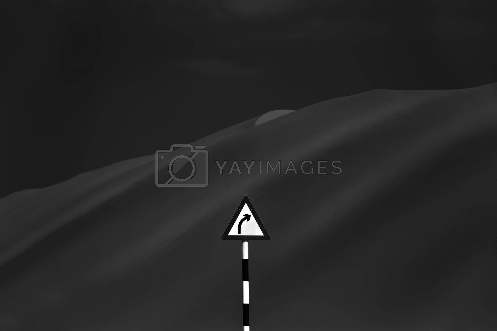 Black and White Photo of a Road Sign Turn among Desert Sand Dunes. Wild Mountains. Choosing Own Way to Escape.