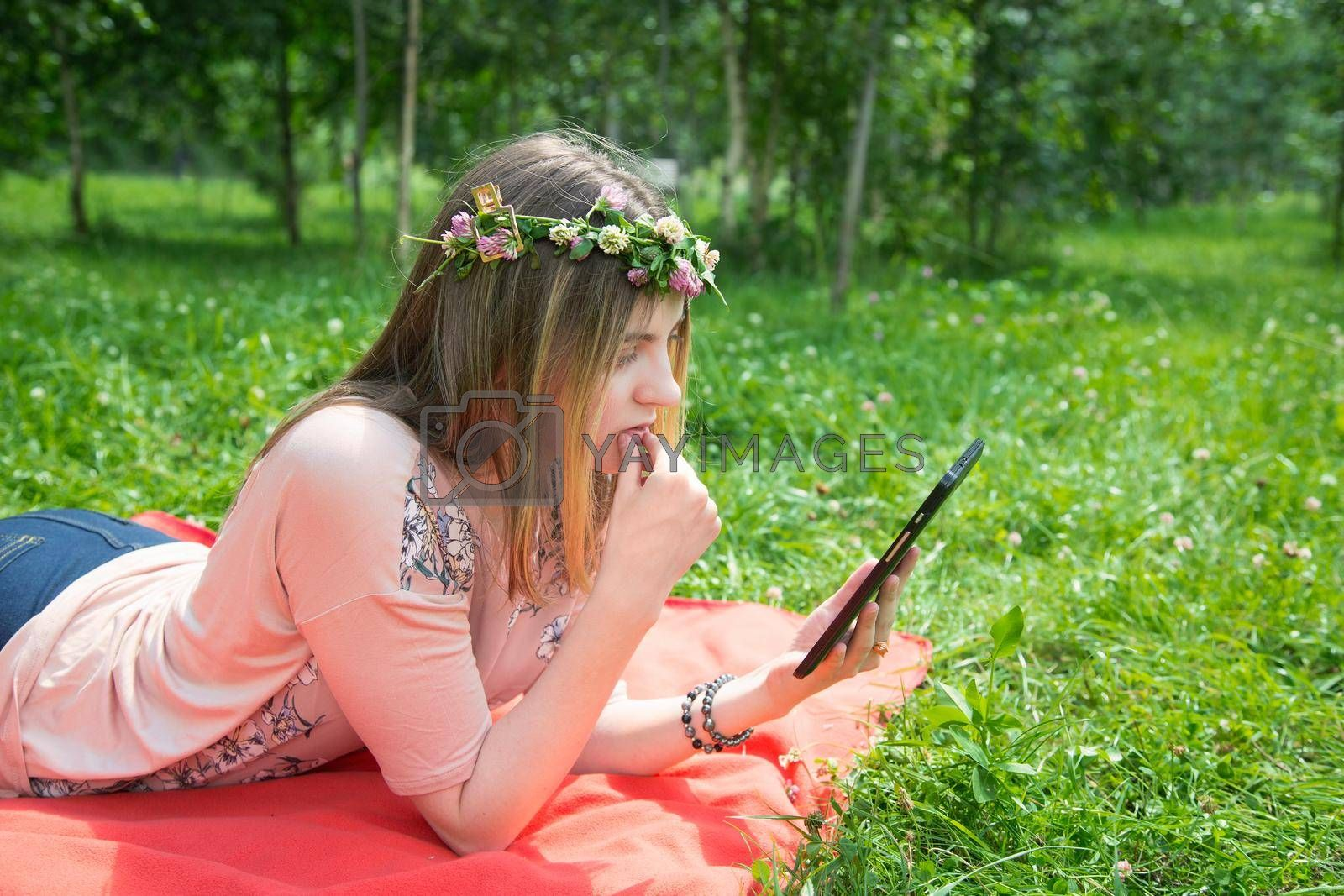 A young girl of 20 years old Caucasian appearance wary with apprehension looks into her mobile phone, sitting on the lawn in the park on a summer day. The girl is dressed in a floral T-shirt and jeans