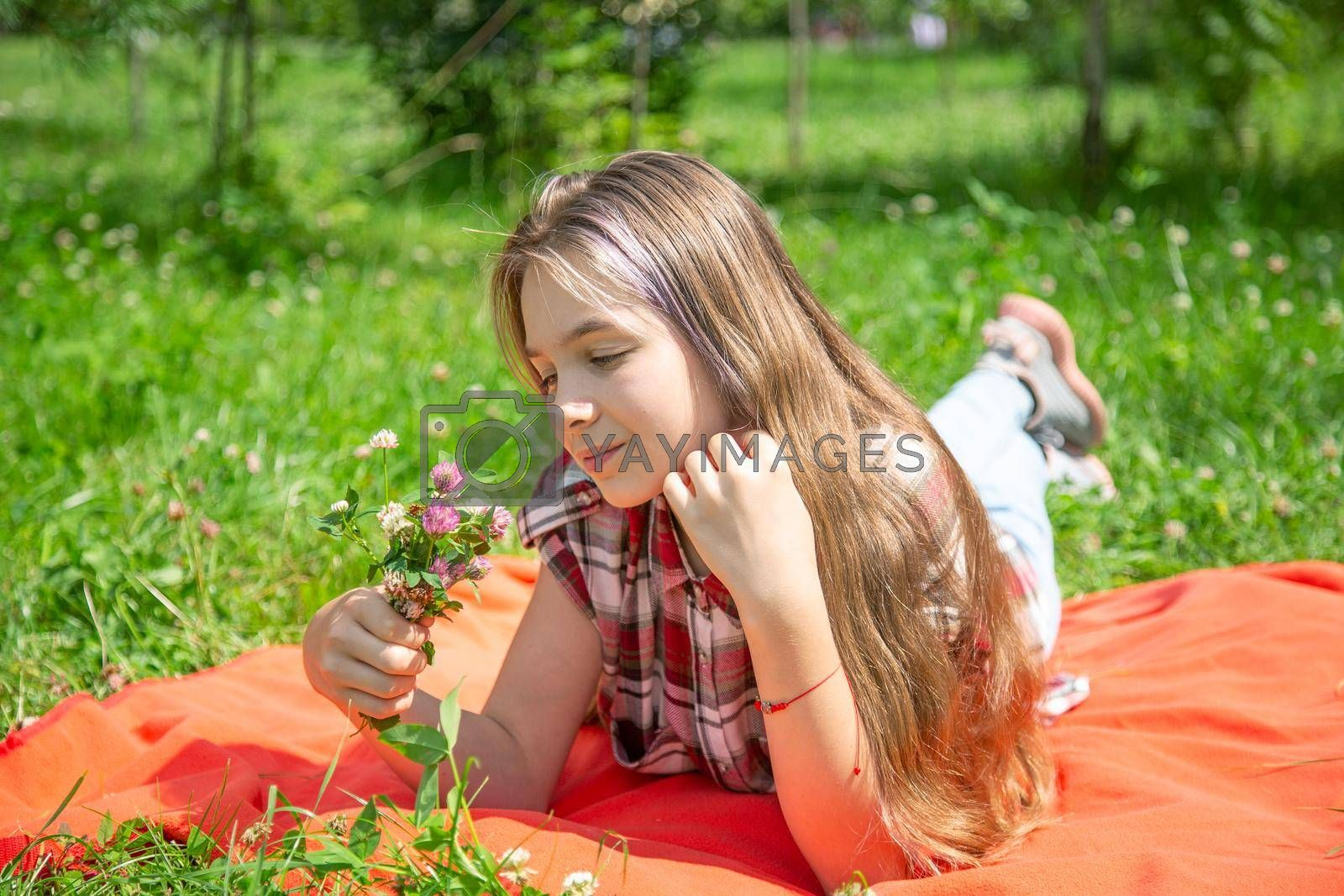 A young girl of 15 years old enjoys a bouquet of wild flowers lying on the lawn by galinasharapova